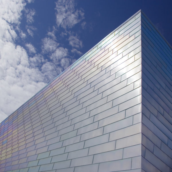 The face of a modern titanium-clad building against a blue sky
